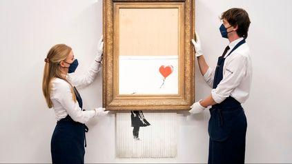 Curadores de arte de la casa londinense de subastas de Sothebys sostienen la obra ahora titulada Love is in the Bin.