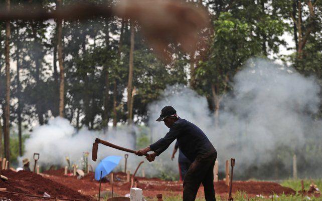 Un sepulturero prepara una tumba para una víctima de COVID-19 en el cementerio de Cipenjo en Bogor