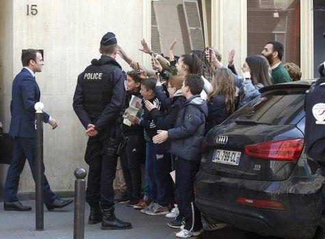 ovación. Emmanuel Macron recibe un entusiasta saludo de un grupo de chicos al salir de su departamento.