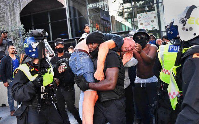 Un manifestante lleva a un contramanifestante herido a un lugar seguro cerca de la estación de Waterloo de Londres durante una protesta de Black Lives Matter en junio de 2020. Fotografía: Dylan Martinez / Reuters