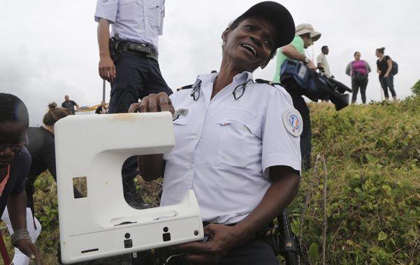 Otra parte. Un oficial de policía sostiene una pieza de plástico encontrada ayer en la costa de la isla de la Reunión.