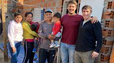 La familia de Julio, Mateo Comba y Luciano Albertengo frente a la nueva casa, en barrio Toba.