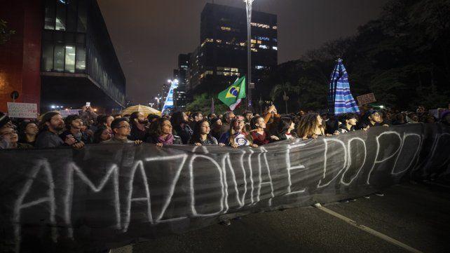 Manifestantes marchan sobre una avenida de San Pablo con una leyenda en portugués: La Amazonia pertenece a la gente.