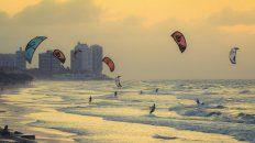 Una playa llena de personas haciendo kitesurf, deporte patentado en 1977 por Gijsbertus Adrianus Panhuise.