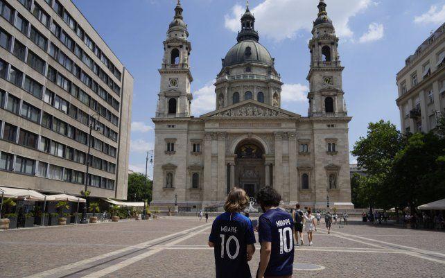 Dos aficionados franceses con camisetas de Kylian Mbappé caminan frente a la Basílica de San Esteban