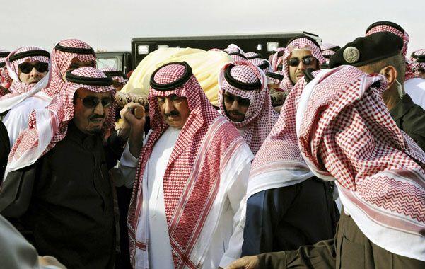 El nuevo rey Salman (de ropa oscura) ayuda a trasladar a su tumba al fallecido rey Abdullah