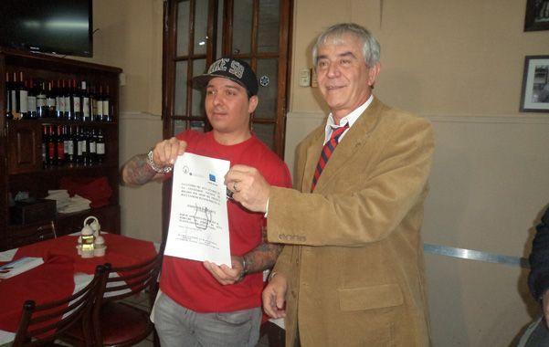 """Pionero. El dueño del comedor Balcarce y el titular de la cátedra muestran la adhesión del local al """"derecho de jarra""""."""