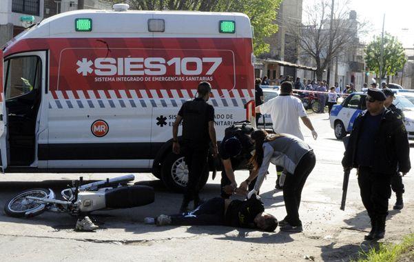 Uno de los ladrones es esposado en la calle estando herido y antes de ser subido a la ambulancia. (Gustavo de los Rios / La Capital)