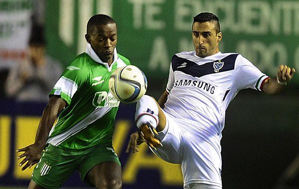El colombiano Mauricio Cuero disputa la pelota con el defensor velezano Hernán Pellerano. (Foto: Télam)