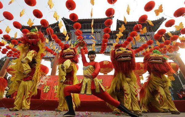 Festival. Artistas desarrollan ayer la danza del león frente a un templo de Beijing