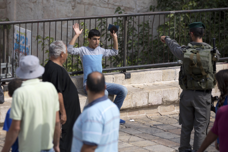 Crece la tensión. Un oficial israelí ordena a un joven palestino que se identifique en Ciudad Vieja de Jerusalén. (NA)