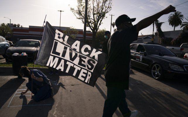 Una mujer con una bandera de Black Lives Matter escribe un mensaje en una acera en Los Ángeles