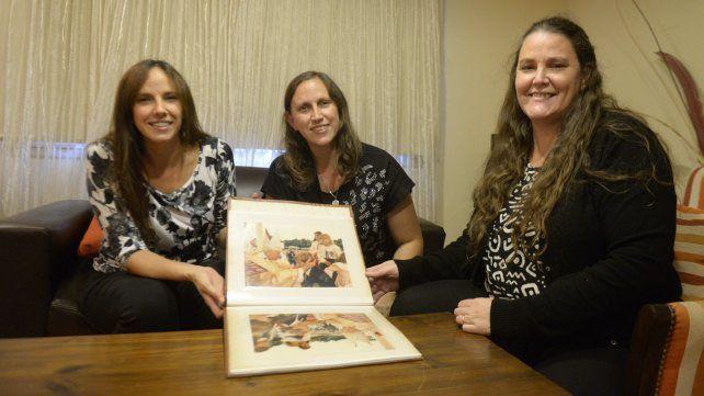 La familia Fernández exhibe el álbum de fotos recibido como obsequio del Arzobispado rosarino.