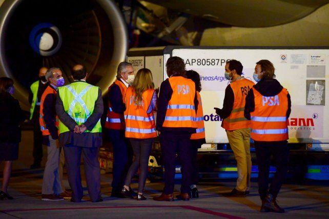 En la pista. El presidente (de perfil) en la noche de este jueves al lado del avión que transportó la carga.