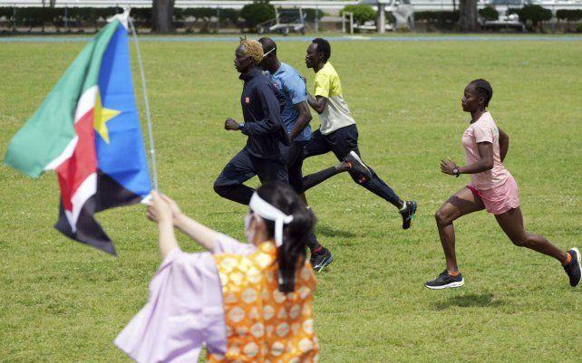 La fan olímpica Kyoko Ishikawa sostiene una bandera de Sudán del Sur para animar al equipo que se entrena para los Juegos Olímpicos y Paralímpicos de Tokio 2020.
