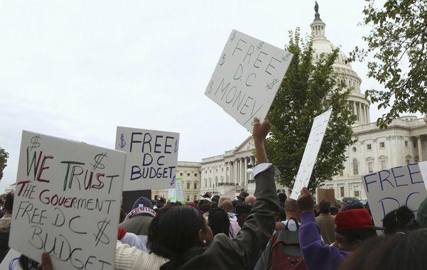 Mal humor. Empleados estatales enviados a casa por la crisis expresan su descontento frente al Capitolio.