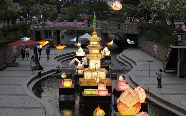 Visitantes caminan cerca de las linternas que se exhiben para la próxima celebración del cumpleaños de Buda el 19 de mayo en la corriente pública en Seúl