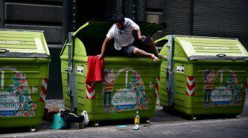Sustento. Un joven sale desde el interior de un contenedor de residuos en Sarmiento al 700.