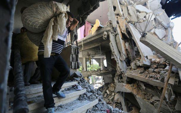 Demolición. Palestinos retiran sus pertenencias de un edificio bombardeado.