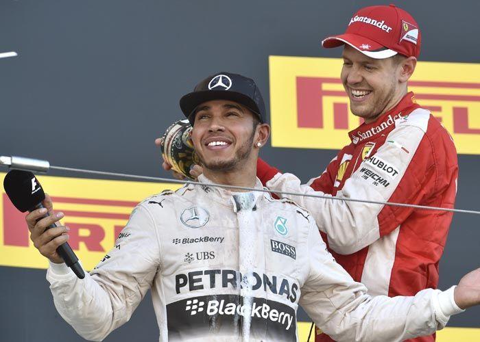 Hamilton celebra el triunfo junto a su compatriota y piloto de Ferrari
