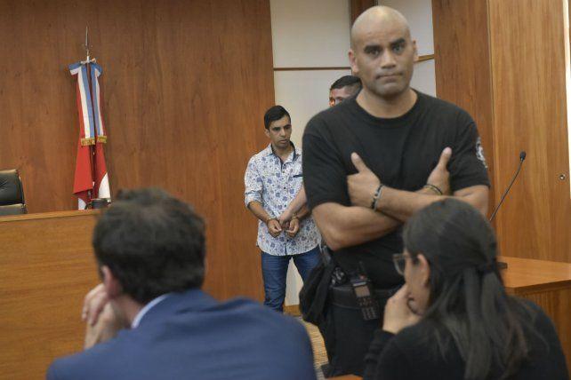 Emiliano Gómez (atrás) es ingresado a la sala de audiencias para conocer el veredicto del tribunal.