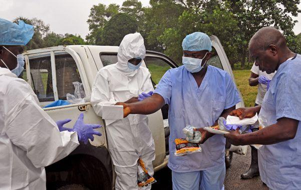 Penoso. Personal sanitario de Nigeria se prepara para asistir a enfermos.