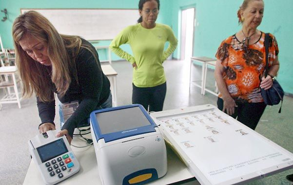 Todo listo. Miembros del consejo electoral ultiman la instalación de las modernas máquinas de votación.