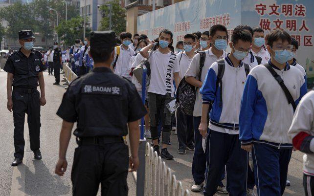 Guardias de seguridad controlan a los estudiantes con máscaras faciales para ayudar a frenar la propagación del coronavirus