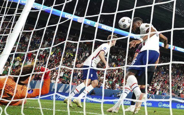 El estadounidense Jordan Siebatcheu Pefok (16) intenta cabecear el balón a la red contra el mexicano Guillermo Ochoa (13) durante el partido de fútbol por el campeonato de la Liga de Naciones de la CONCACAF