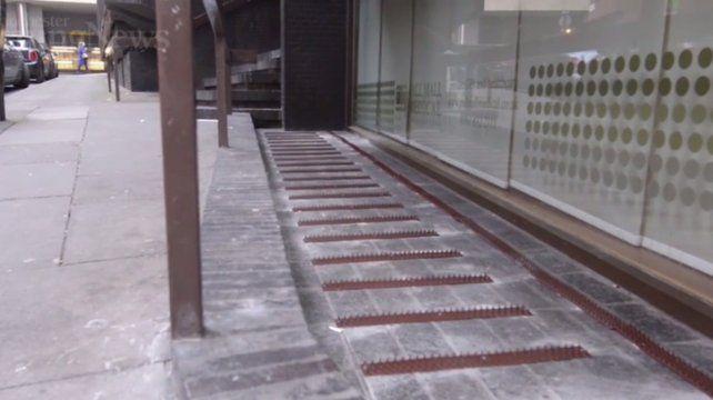Un complejo de oficinas puso clavos para que los indigentes no duerman frente al edificio