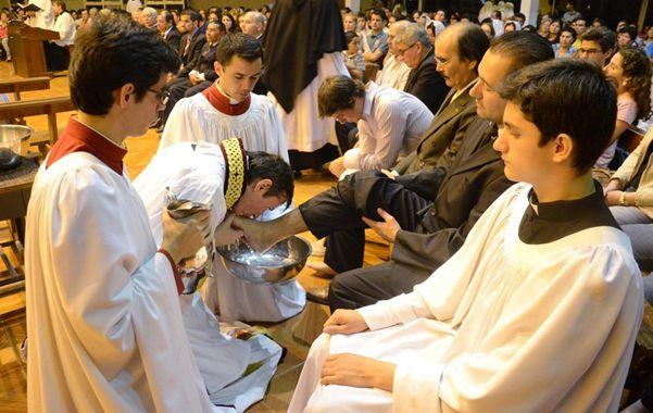 En la mira. El sacerdote Urrutigoity besa los pies de los fieles durante la liturgia.