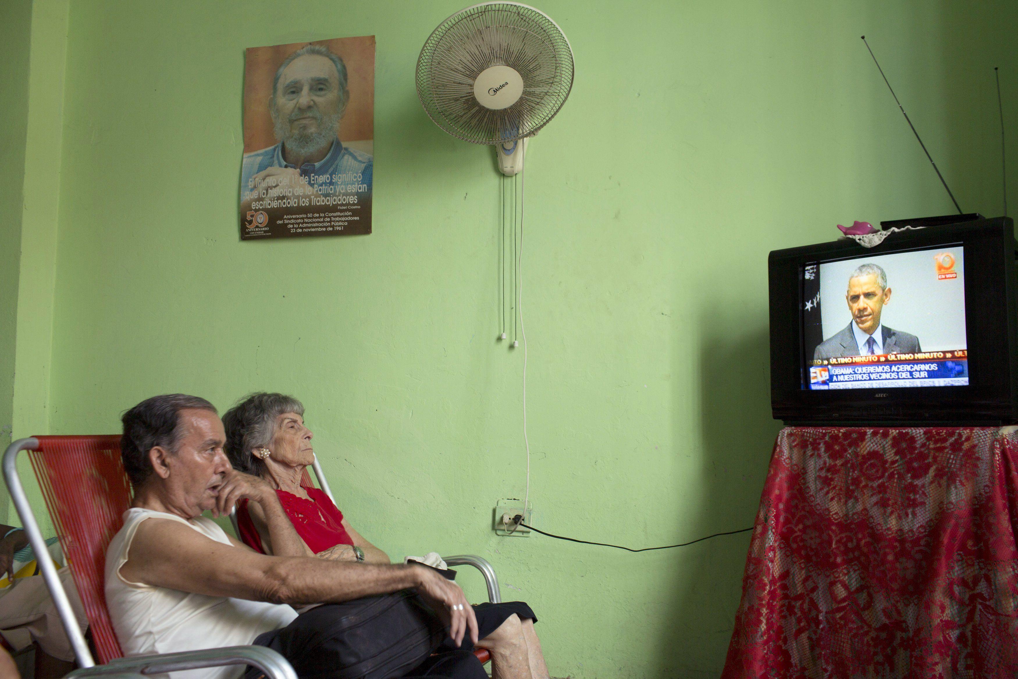 Expectativas. Una pareja cubana mira por televisión el anuncio de Obama.