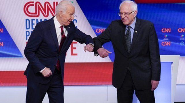 Coditos. Biden y Sanders se saludan según el modo que ha impuesto la pandemia antes de iniciar el duelo.