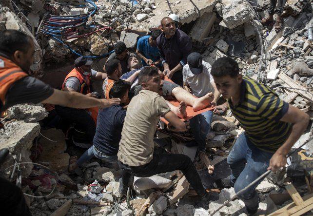 Rescatistas retiran a un herido grave de entre los escombros.