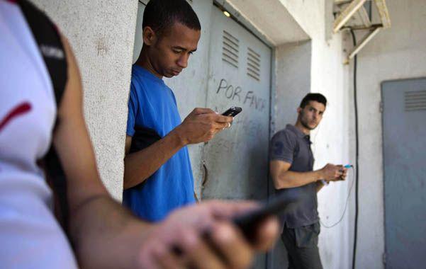 Sin señal. Cubanos buscan conectar su celular en el patio de un comercio.