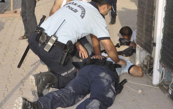 Un policía turco intenta ayudar a un compañero herido por la explosión de morteros en la volátil región fronteriza con Siria.