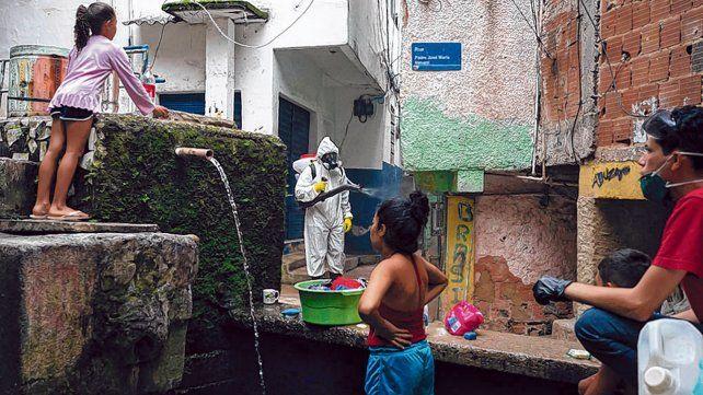 Precariedad. Dos niñas buscan agua en una vertiente mientras un sanitario fumiga en una favela de Río.