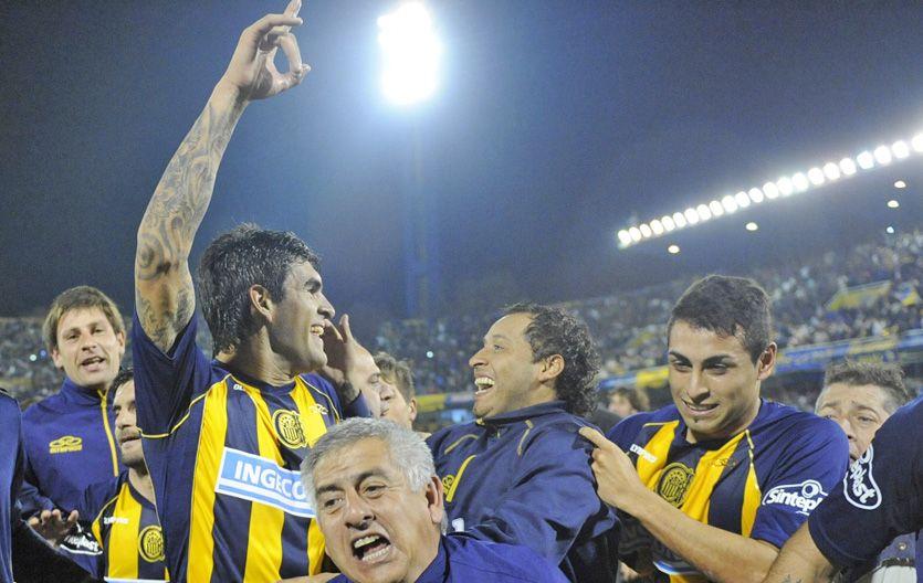Toledo intercambia sonrisas con el Zapito Encina en la vuelta olímpica del equipo canalla.