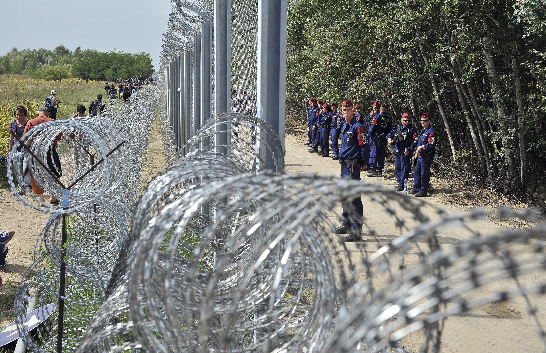 Contención. Oficiales húngaros montan guardia frente a la alambrada fronteriza con la vecina Serbia.