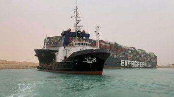 Un remolcador pasa junto al buque portacontenedores llamado Ever Given, operado por Evergreen Marine, después de que encalló en el extremo sur del Canal de Suez, bloqueando el tráfico de navegación en ambas direcciones. El barco giró de costado en el Canal mientras se dirigía de China a Rotterdam.