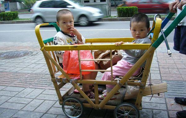 Gemelos paseados en cochecito. La política de un solo hijo en China varía según las regiones.