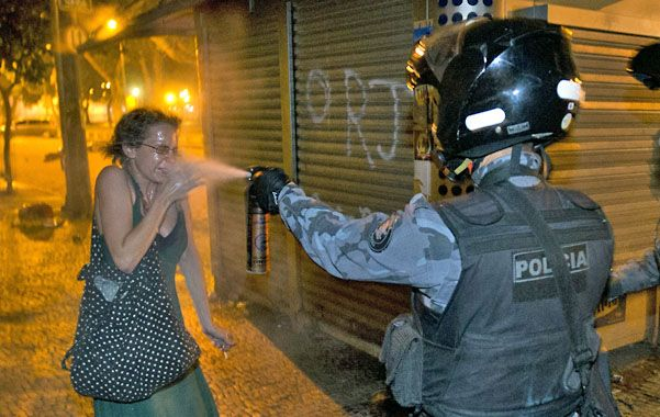 Represión. Un policía de Río esparce gas pimienta a una manifestante. San Pablo vivió otra noche de protesta.