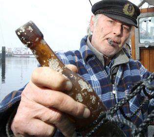 El pescador Konrad Fischer muestra su hallazgo de una botella con un mensaje lanzada al mar en 1913 (Foto :AFP)