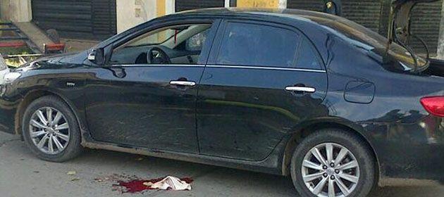 El Toyota Corolla que fue atacado por los motochorros. En el piso un trapo con sangre