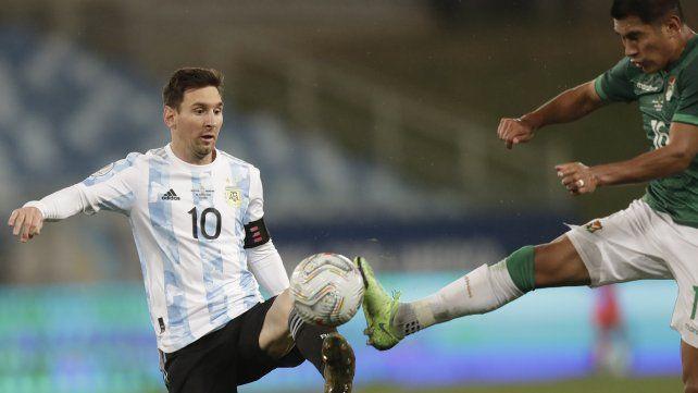 Lionel Messi y Erwin Saavedra luchan por el balón en el estadio Arena Pantanal de Cuiabá, Brasil.AP Photo / Andre Penner.