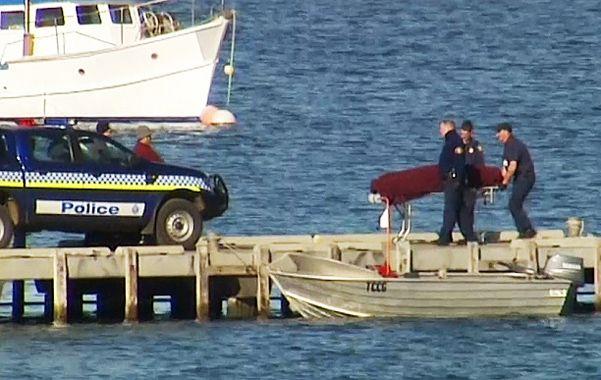 Penoso. La policía de la isla María traslada el cuerpo de la víctima.