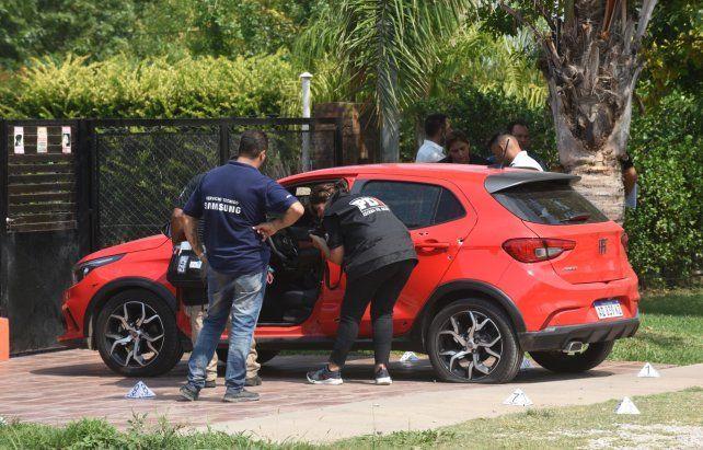 Efectivos de la Agencia de Investigación Criminal levantan rastros del auto de la mujer baleada.