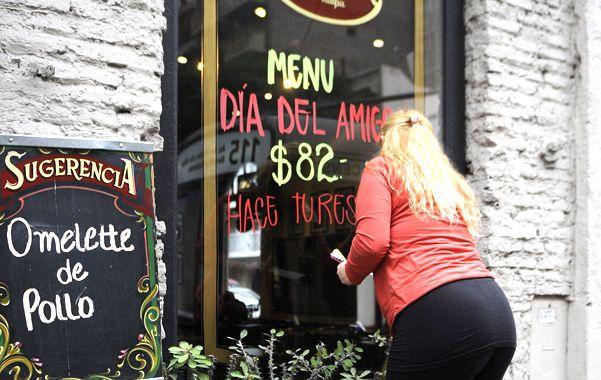 A prepararse. Una comerciante pintaba ayer la oferta de menú para el Día del Amigo en la vidriera de un bar.