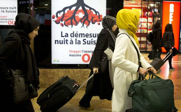 Sin bienvenida. Mujeres islámicas en una estación de trenes de Ginebra pasan ante un afiche contra la inmigración.