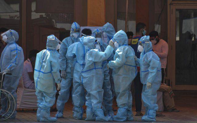 Trabajadores de la salud y voluntarios esperan recibir a los pacientes fuera de un hospital que se instaló en un Sikh Gurdwara